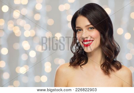 beauty, make up and people concept - happy smiling young woman with red lipstick over holidays lights background