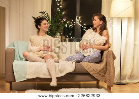 friendship, hygge and pajama party concept - happy female friends or teenage girls talking at home