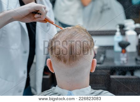 The Barber Is Cutting A Man With Scissors. Close Up.