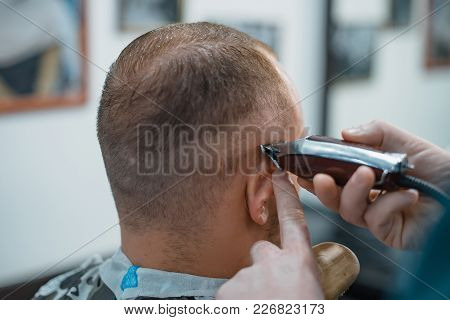 Man Gets A Cool Haircut In Barbershop. Barber Cuts Machine.