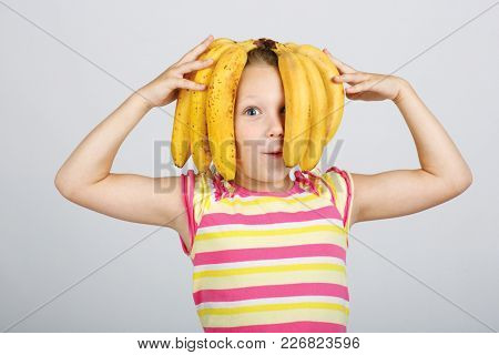 Funny humorous photo. Little cheerful little girl plays with a banana hairdo