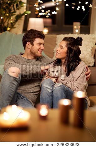 pets, hygge and people concept - happy couple with cat at home