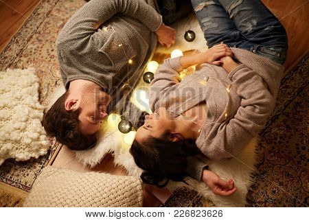 leisure, hygge and people concept - happy couple with garland lying on floor at home