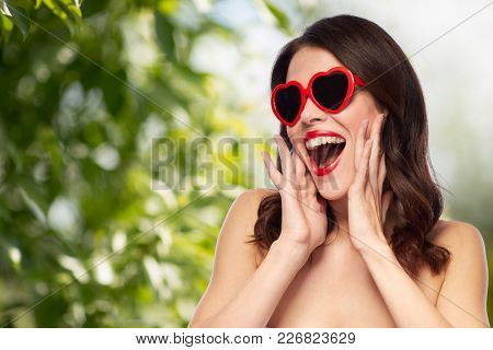 valentines day, beauty and people concept - happy smiling young woman with red lipstick and heart shaped sunglasses over green natural background