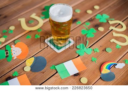 st patricks day, holidays and celebration concept - glass of draft beer, shamrock and gold coins on wooden table