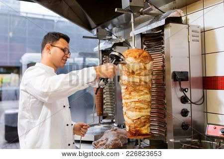 fast food and cooking concept - chef slicing doner meat from rotating spit at kebab shop