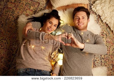 leisure, hygge and people concept - happy couple with garland lying on floor at home and making hand heart gesture