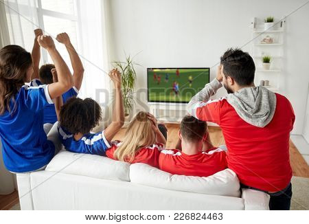 leisure, sport and entertainment concept - happy friends or football fans watching soccer game on tv and celebrating victory at home
