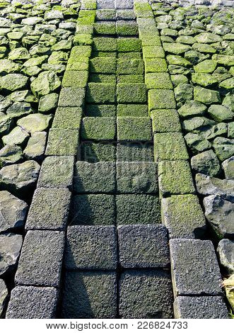 Symmetrical Image Of Slippery Mossy Stone Steps Leading To Water