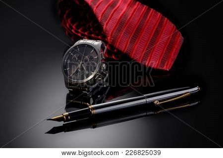 Father's Day Or Business Concept Image. Elegant Man's Watch, Fountain Pen And Red Tie On Black Gradi