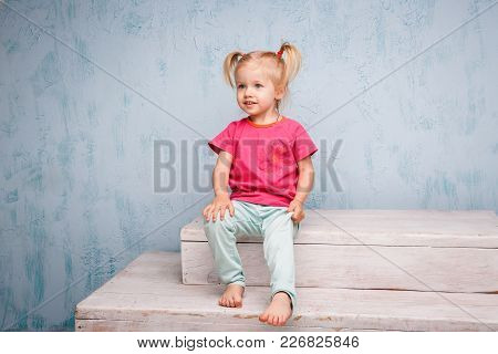Little Funny Blue-eyed Girl Child Blonde With A Haircut Two Ponytails On Her Head Sitting On A Gossi