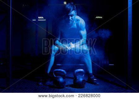 Weightlifter clapping hands and preparing for workout at a gym. Focus on dust