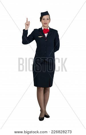 Stewardess In Full Growth On A White Background Stands And Shows The Index Finger Up