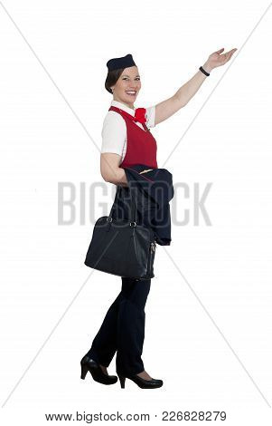 Stewardess In Full Growth On A White Background Steps, Smiles And Shows A Hand Forward And Upwards