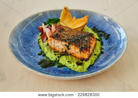 Large Juicy Roasted Fatty Piece Of Salmon Steak On A Cushion Of Vegetable Puree, Decorated With Radi