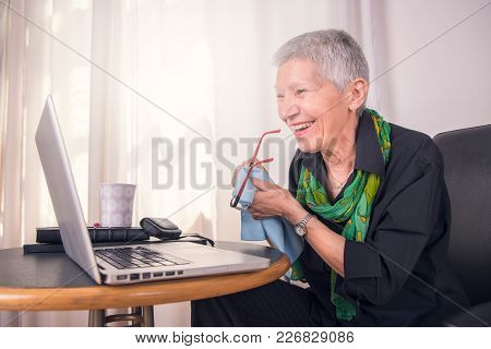 Happy Senior Woman Using A Laptop And Wiping Her Glasses Clean