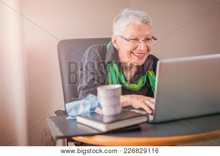 Happy Senior Woman Using Laptop To Browse Internet And Amuse Herself With Funny Content