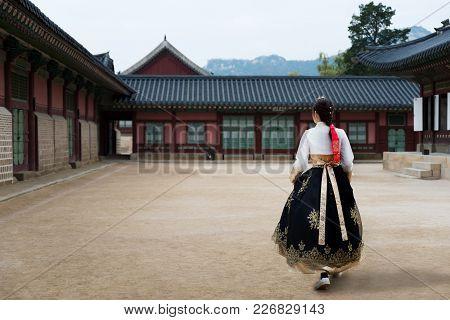 Asian Korean Woman Dressed Hanbok In Traditional Dress Walking In Gyeongbokgung Palace In Seoul, Sou