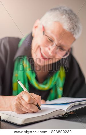 Senior Old Woman Writing Down Letters On A Piece Of Paper, Recording A Journal Or Diary Entry Or Wri