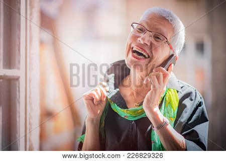 Lovely Senior Lady Having A Fun Conversation With Her Friend Or A Family Member Over Her Cell Phone