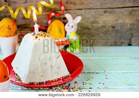 Easter Quark Dessert Decorated With Colorful Sprinkles And Lighted Candle
