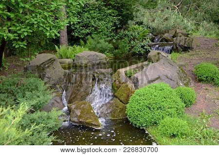 The Beautifully Landscaped Garden With A Stream And Boulder.