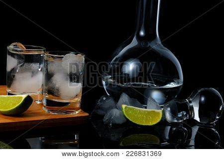 Two Shots Of Strong Alcohol Near Decanter. Two Shots With Strong Alcohol On A Wooden Board With Ice