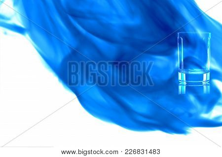 Small Empty Shot Of Vodka Or Tequila On White Background Enveloped In Puff Of Blue Smoke. Place For