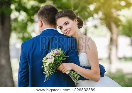 Bride And Groom At Wedding Day Walking Outdoors On Spring Nature. Bridal Couple, Happy Newlywed Woma