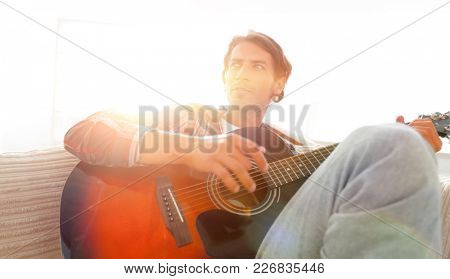 modern guy with guitar sitting on sofa in living room.
