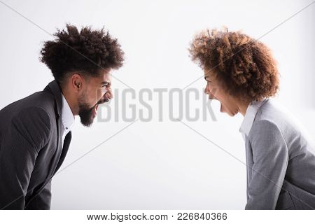 Close-up Of Two Angry Young Business Partner Shouting At Each Other In Office