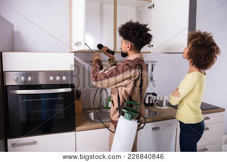 Woman Looking At Pest Control Worker Spraying Insecticide On Shelf Of Domestic Kitchen