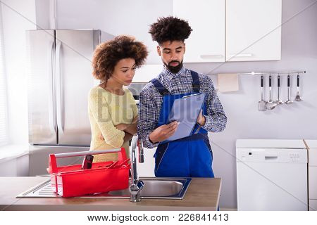 Young Male Plumber Looking At Woman Signing Invoice In Kitchen