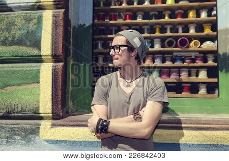 Young Man Waiting On A Street In Front Of Ribbon Shop