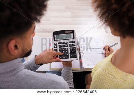 High Angle View Of Young Couple Sitting On Sofa Analyzing Bill