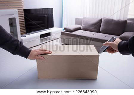 Person's Hand Opening Cardboard Box