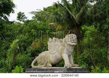 Statue In Bali Indonesia With Jungle And Palm Trees In The Back