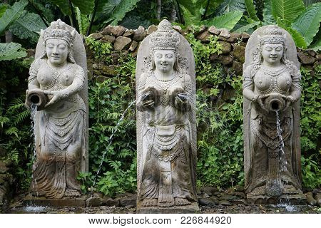 Statues In Bali Indonesia Of A Fountain With Jungle In The Back
