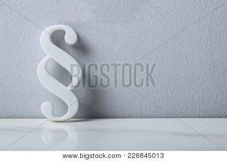Close-up Of A Paragraph Symbol Leaning On White Wall