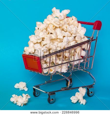 Popcorn In A Shopping Trolley. A Bunch Of Popcorn On A Blue Background. Surrealistic Concept.