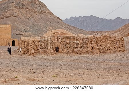 Yazd, Iran - May 4, 2015: Disused Building At The Foot Of The Hill And The Tourists Sightseeing The