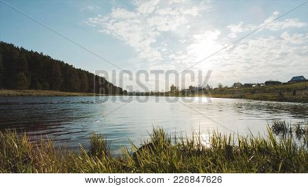 Sun Over The River In The Morning. Video. Green Lawn Near River In The Forest. Sunset Over Water. Na