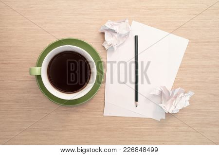 A Green Cup Of Coffee On The Background Of A Table And A White Blank Piece Of Paper, A Pencil And Cr