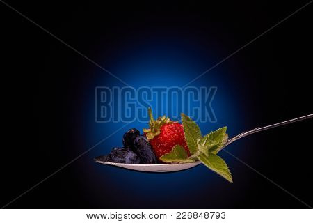 Ripe sweet strawberry, honeysuckles and branch of mint on a spoon on a dark background.