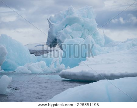 Baby Blue, Gray Blue And Gray Icebergs In Esperanza In Antarctica Floating In The Steel Blue Water O