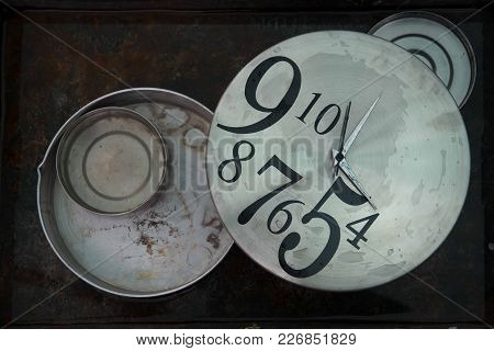 Huge Round Gray Wall Clocks With Black Asymmetric Figures Lie Among The Gray Circles Of Metal On A B