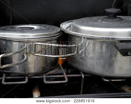 Close Up Of Stainless Steel Sauce Pans On A Camp Stove With Flames Licking Their Sides.