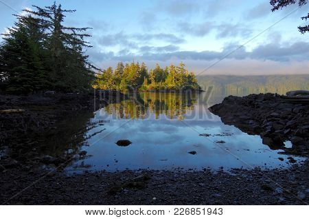 Tranquil Early Morning Reflection Of Island And Trees Seen From The Bay At Nolan Point, Northern Van