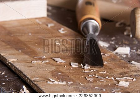 Wood Carving Chisel On Workbench Among Scattered Wood Chips