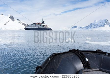 A Ship Anchored In Paradise Bay Antarctica, Photographed From A Zodiak Boat. Snow Covered Mountains